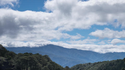 Foggy morning landscape with moving clouds at blue sky over forest and mountain Footage