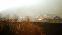 Houses, smoke, sun, mountains in fog, idyllic landscape Footage
