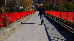 Woman with red hat walking on bridge, rear Footage