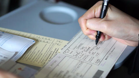 Tourist's hand filling custom immigration form. Writing form on plane before lan Live Action