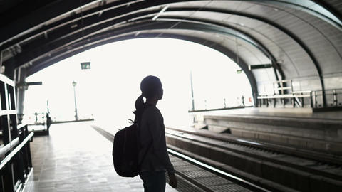 Silhouette for tourist girl backpacker waiting for train at the open station, tr Footage