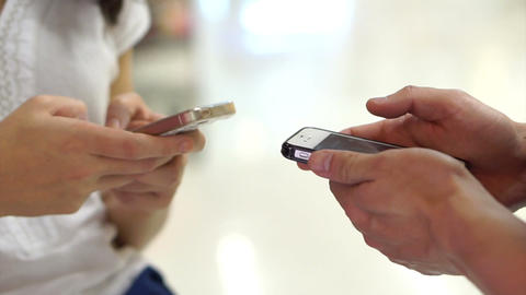 Two People Using Touchscreen Smart Phone In Public. Close-up Of Hands Typing On  stock footage