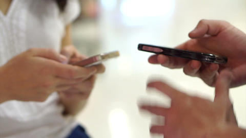 two people using touchscreen smart phone in public. Close-up of hands typing on  Footage