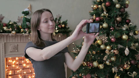 Young pretty woman taking selfie at home while sitting near Christmas tree Footage