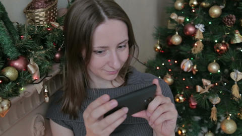 Woman using her mobile phone at christmas at home in the living room Footage