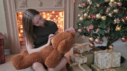 Young woman sitting on the floor and hugs, toss, touch a big teddy bear in Chris Footage
