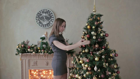 Beautiful teenager girl decorating the Christmas tree Footage
