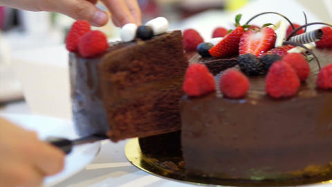 Female hand cutting on pieces the Sticky chocolate cake with fresh strawberries  Footage