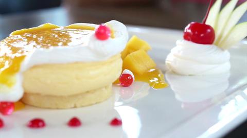 Eating Mango Cheese Cake on white plate with fresh fruit decoration Footage