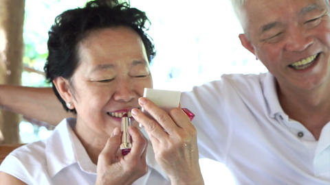 Happy lovely Asian senior couple, woman do make up lipstick and show to her husb Footage