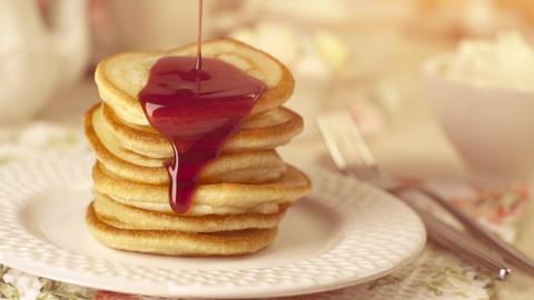 Stack of home-cooked pancakes with pouring jam Footage