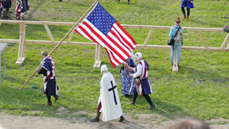 Man in medieval outfit is carrying US flag Live Action