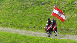 Two medieval knights from Austria walk with flag Live Action