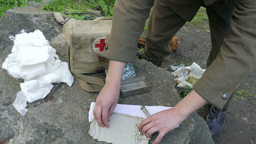 Paramedic soldier from WW2 opening historic first aid kit Footage