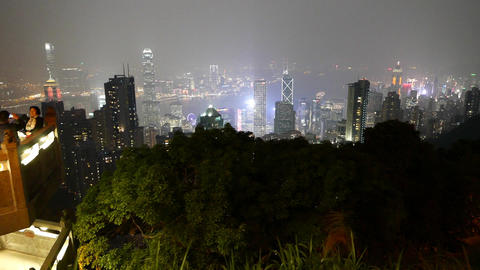 Night Hong Kong panorama beyond green dark trees green trees, pan shot Footage