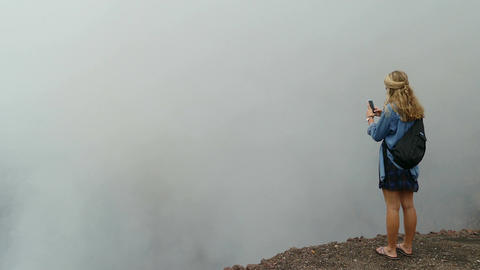 Blond lady taking picture of crater the Masaya vulcano Stock Video Footage