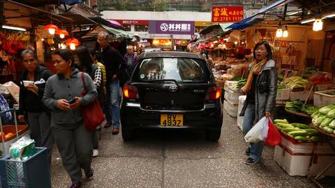 Following black car, drive through street market Stock Video Footage