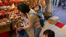 Chinese child waiting with mom and baby, handling toy Stock Video Footage