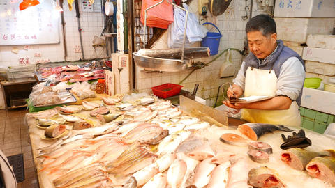 Store stall at sea food market, seller weight fresh fish on hanging pan Footage