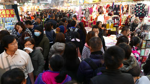 Asian people slowly rush through crowded market street aisle, overhead shot Footage