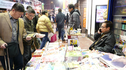Focusing on two man looking up book stall on busy night... Stock Video Footage