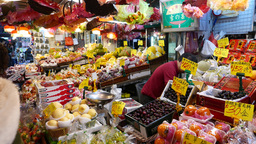 Seller serves clients of fruit and vegetable store in open air market Footage
