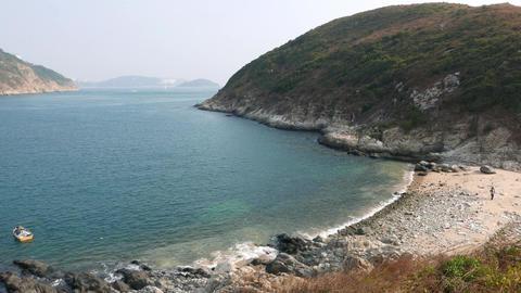 Dry grass on wind, rocky slope of hill, sea bay far below... Stock Video Footage