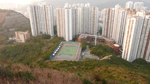 Football field and dense building area down the hillside.... Stock Video Footage