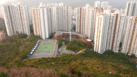 Football field and dense building area down the hillside. View from top Footage