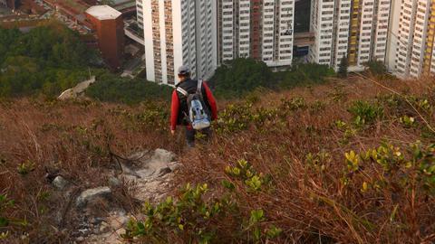 Hiker man climb down steep path at hillside. Buildings... Stock Video Footage
