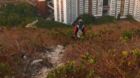 Hiker man climb down steep path at hillside. Buildings area on back, high angle Footage