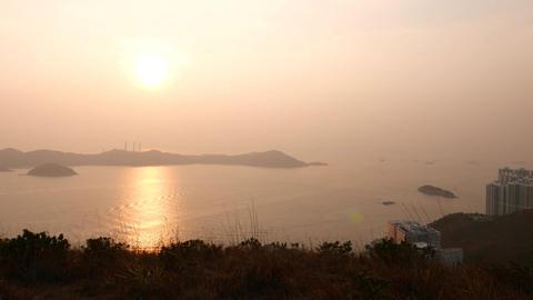 Beautiful seascape early evening sunset, sun light through haze, hill top Footage