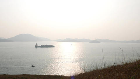 Cargo ship on shiny harbour waters. Island in fog on... Stock Video Footage