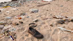 Rocky beach full of colorful debris, thrown out by the... Stock Video Footage