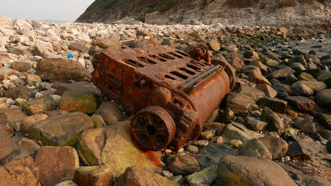 Ship engine rusted skeleton on rocky shore, close up Footage