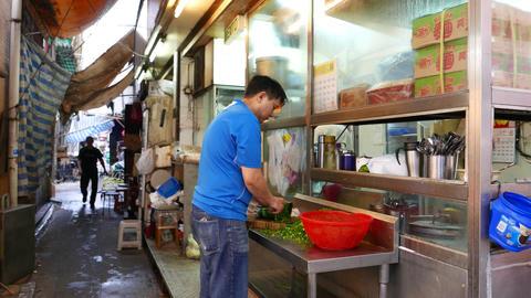 Kitchener shreds onion bunch on street desk, side... Stock Video Footage