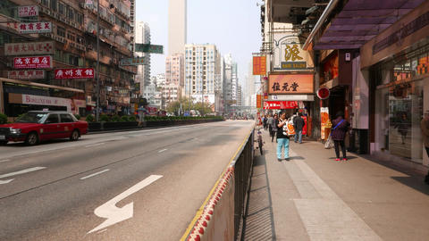 POV walk shot along Hong Kong street pavement at day time. Sparse road traffic Footage