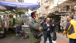 Chinese man speaking on phone on crowded street Stock Video Footage