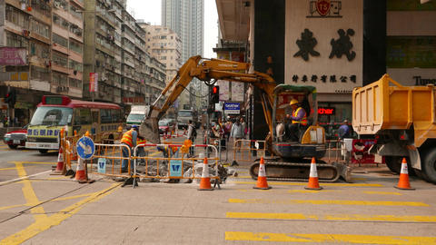 Small excavator work at lively city street, remove concrete debris to truck Footage