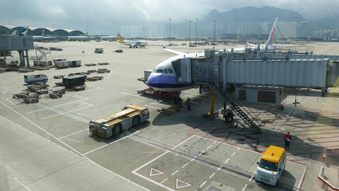 Airplane parked at inner ramp, jet bridge connected, tilt... Stock Video Footage
