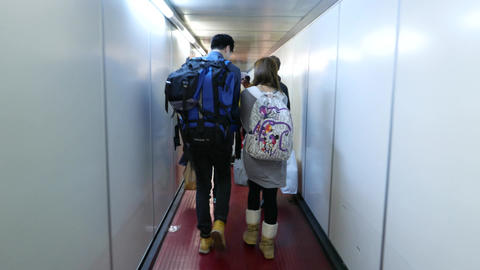 Young travellers couple walk out plane by jet bridge,... Stock Video Footage