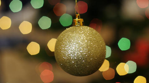 Christmas golden ball rotates at background bokeh Stock Video Footage