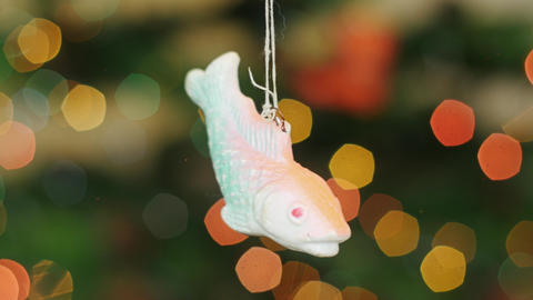 Christmas fish toy shakes at background bokeh Stock Video Footage