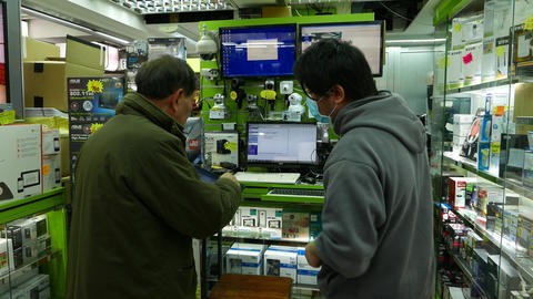 Aged chinese client choos laptop in small shop section Stock Video Footage