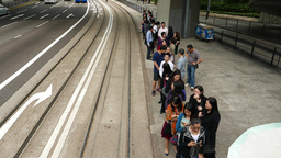 Passengers queue up to tram stop, walk towards in line, tramway departs away Footage