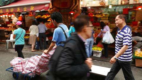 Woman come at street market, loader man push cart along Stock Video Footage