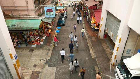 People walk along Wan Chai road, street market stalls, garage doors Footage