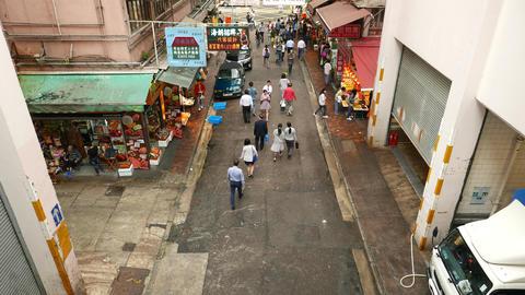 People walk along Wan Chai road, street market stalls,... Stock Video Footage