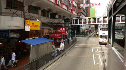 Jewellery stores along sidewalk seen from double decker tram move along road Footage