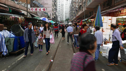 POV walk through street market in Hong Kong, many people mill around Footage